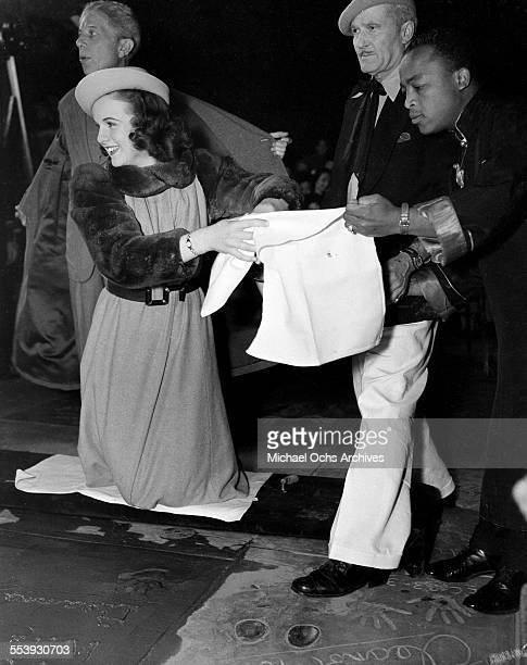 Actress Deanna Durbin wipes off her hands after making a hand print in cement in front of Grauman's Chinese Theater with the help of Jean W Klossner...