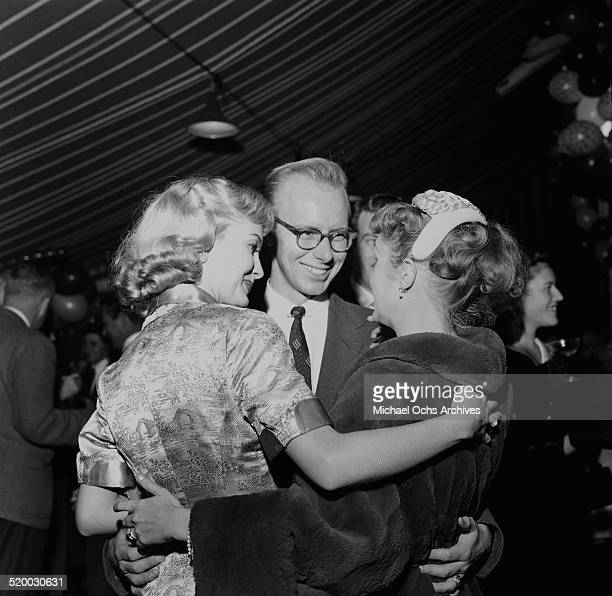 Actress Debbie Reynolds greets Lori Nelson and Leon Tyler during a party by Mike Todd in Los AngelesCA