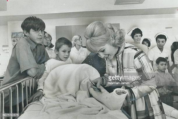 Actress debbie reynolds signs on a new cast Actress Debbie Reynolds incribes her autograph on the leg cast of 7yearold Wayne Dance of Pickering...
