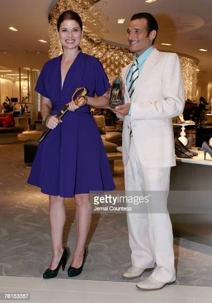 Actress Debra Messing and Actor Phillip Bloch pose after cutting the ribbon at the Unveiling of SAKS Fifth Ave's '10022SHOE' its new designer shoe...