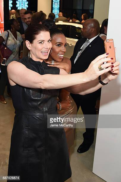 Actress Debra Messing and singer Kelly Rowland take a selfie as Cadillac celebrates the grand opening of Cadillac House on June 1 2016 in New York...