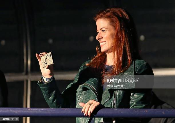 Actress Debra Messing looks on with her cell phone as Will Chase of the cast of 'Nashville' performs at Best Buy Theater on May 6 2014 in New York...