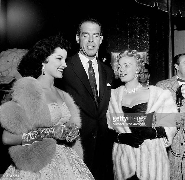 Actress Debra Paget poses with Fred MacMurray and wife June Haver as they attend the movie premiere of Prince Valiant at Romanoff's in Los AngelesCA