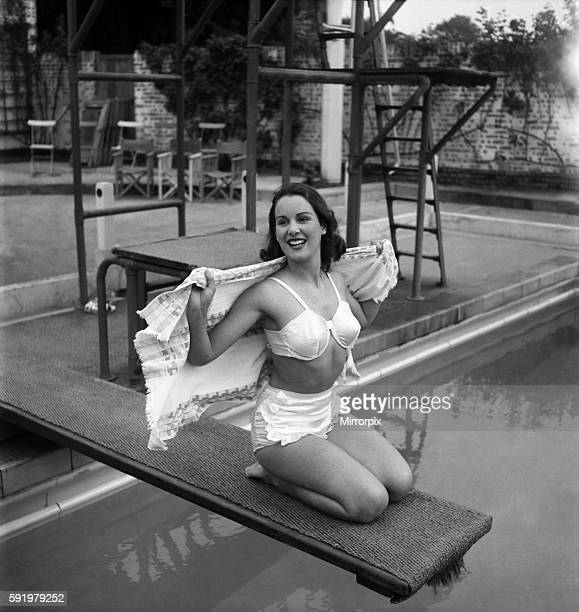 Actress Deidre De Peyer poses sitting on the diving board at Roehampton swimming pool. June 1949 O20117-003