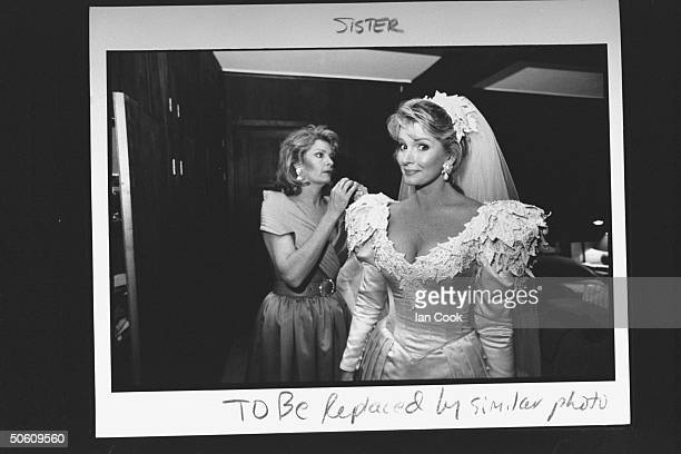 Actress Deidre Hall wearing gorgeous wedding dress designed by Nolan Miller chatting w her matron of honor actress Andrea Hall Gengler who is her...