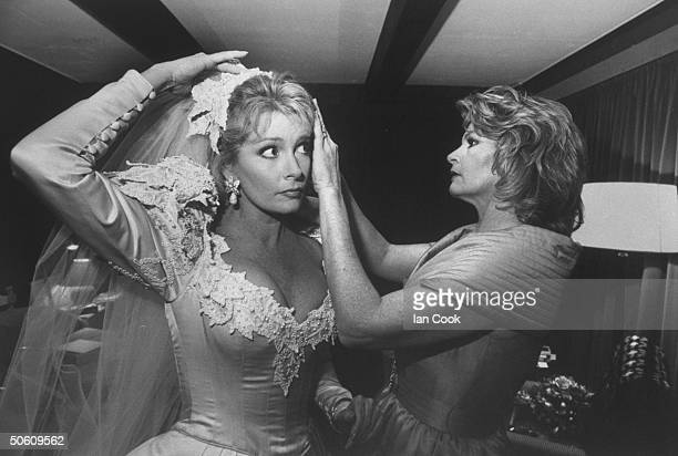 Actress Deidre Hall wearing gorgeous wedding dress designed by Nolan Miller getting a veil adjustment from her matron of honor actress Andrea Gengler...