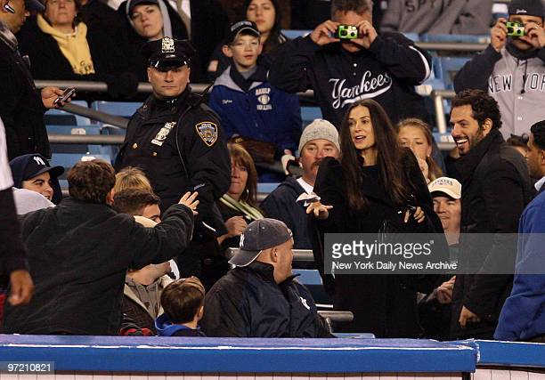 Actress Demi Moore throws a batting glove to another fan as she leaves the game New York Yankees against the Tampa Bay Rays at Yankee Stadium