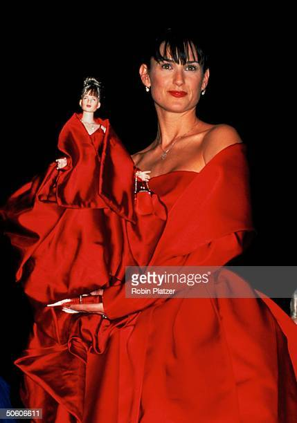 Actress Demi Moore wearing red silk gown by Dolce Gabbana while holding doll of her by Robert Tonner wearing same outfit at AmFAR dinner doll auction