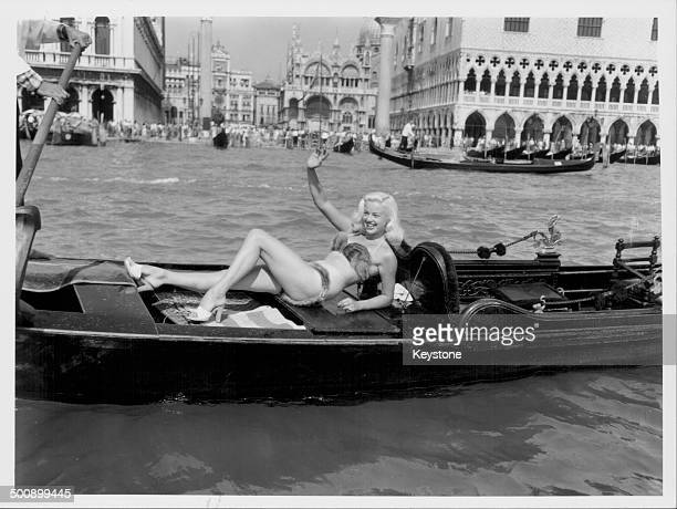 Actress Diana Dors modeling a mink bikini on a gondola, waving to the crowds as she floats along the canal, at the Venice Film Festival, Italy,...
