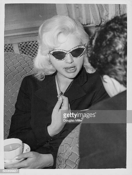 Actress Diana Dors wearing sunglasses and drinking tea at a reception at the Dorchester Hotel London November 12th 1956