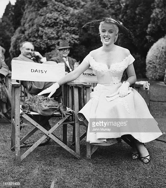 Actress Diana Dors with her co-star Daisy, on the set of the film 'An Alligator Named Daisy' at Pinewood Studios, July 1955. Behind them, actor Jimmy...