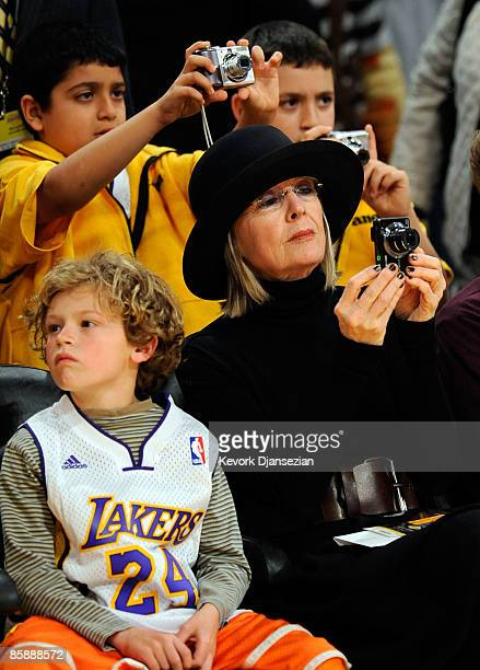 Actress Diane Keato with her son Duke looking on takes a picture of Kobe Bryant of the Los Angeles Lakers before the strat of the game against the...