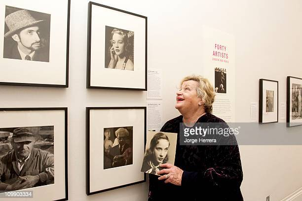 Actress director and producer Sylvia Syms poses next to her portrait by Ida Kar during the private view of 'Ida Kar Bohemian Photographer 195268' at...
