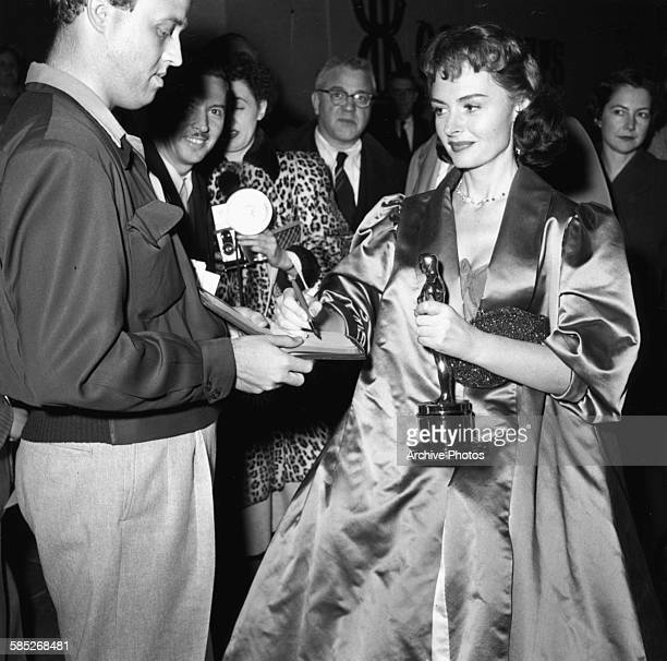 Actress Donna Reed holding her Oscar for the film 'From Here to Eternity' signing an autograph for a fan as she leaves the 26th Academy Awards March...