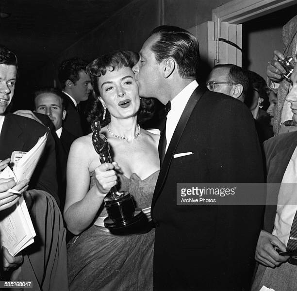 Actress Donna Reed holding her Oscar for the film 'From Here to Eternity' being kissed on the cheek by fellow winner William Holden at the 26th...