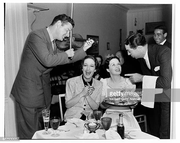 Actress Dorothy Lamour smiles as her husband Herbie Kaye serenades her and actress Gail Patrick during a party in Los Angeles California