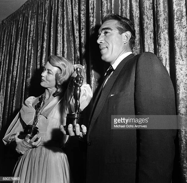 Actress Dorothy Malone and actor Anthony Quinn pose with their Oscars for Best Supporting Actress for Written on the Wind and Best Supporting Actor...