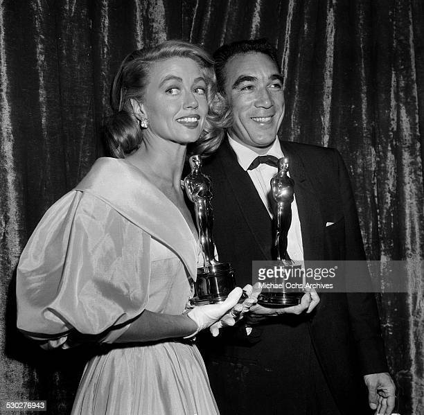 Actress Dorothy Malone and actor Anthony Quinn pose with their Oscars for Supporting Actress for Written on the Wind and Supporting Actor for Lust...