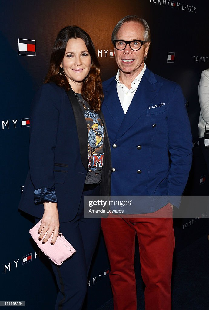 Actress Drew Barrymore (L) and designer Tommy Hilfiger arrive at the Tommy Hilfiger West Coast Flagship Grand Opening Event at Tommy Hilfiger West Hollywood on February 13, 2013 in West Hollywood, California.