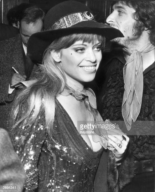 Actress Edina Ronay wearing a shiny dress and felt hat at the London Pavilion for the world premiere of the film 'Here We Go Round The Mulberry Bush'