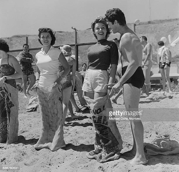 Actress Elaine Stewart and Adelle August enter a sack race as actor Hugh O'Brian gives support during the Thalians Beach Ball in MalibuCalifornia