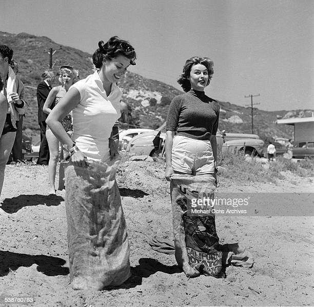 Actress Elaine Stewart and Adelle August enter a sack race during the Thalians Beach Ball in MalibuCalifornia