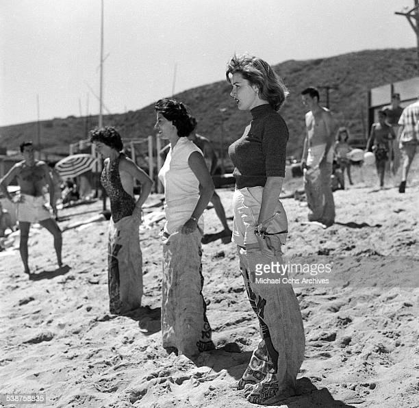 Actress Elaine Stewart and Adelle August get ready for a sack race during the Thalians Beach Ball in MalibuCalifornia