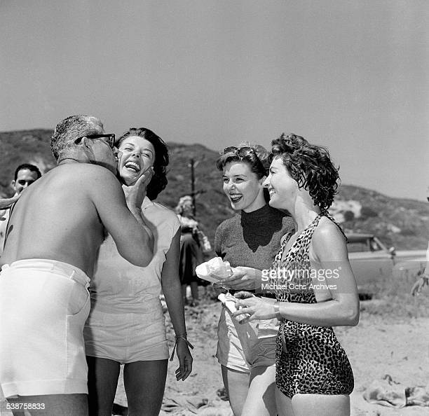 Actress Elaine Stewart looks on as Adelle August is kissed during the Thalians Beach Ball in MalibuCalifornia