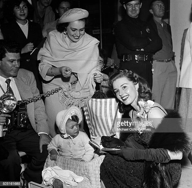 Actress Elaine Stewart poses and signs her autograph for a little fan during an event in Los AngelesCA
