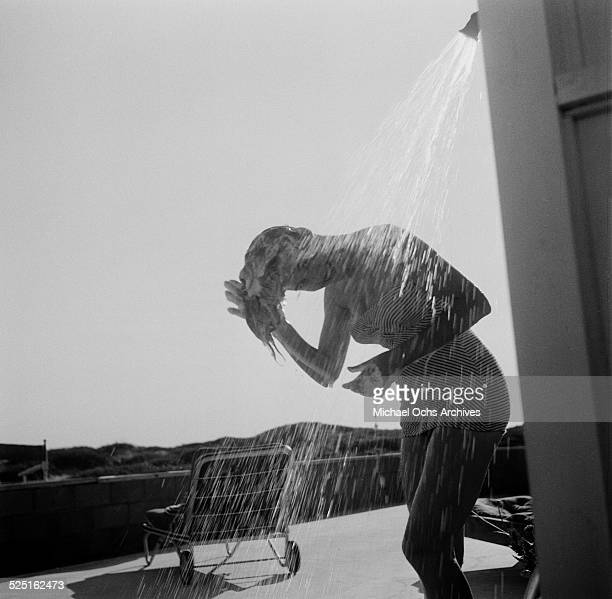 Actress Elaine Stewart poses as she washes her hair at the beach with an umbrella in Los AngelesCA