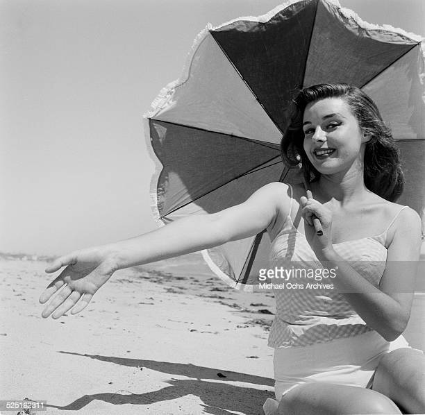 Actress Elaine Stewart poses at the beach with an umbrella in Los AngelesCA