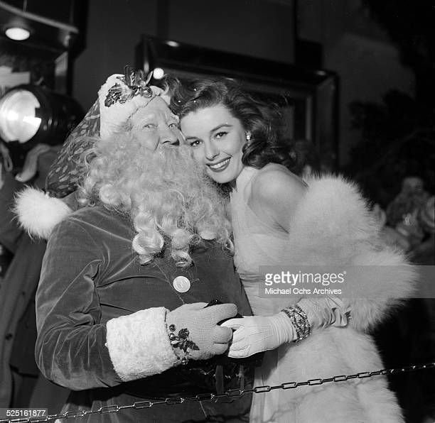 Actress Elaine Stewart poses with Santa Claus during the premiere for Knights of the Round Table in Los AngelesCA