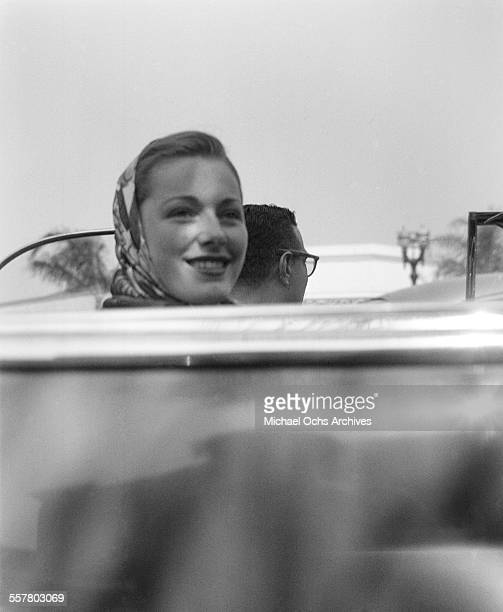 Actress Eleanor Parker smiles as she rides in a convertible car in Los Angeles California
