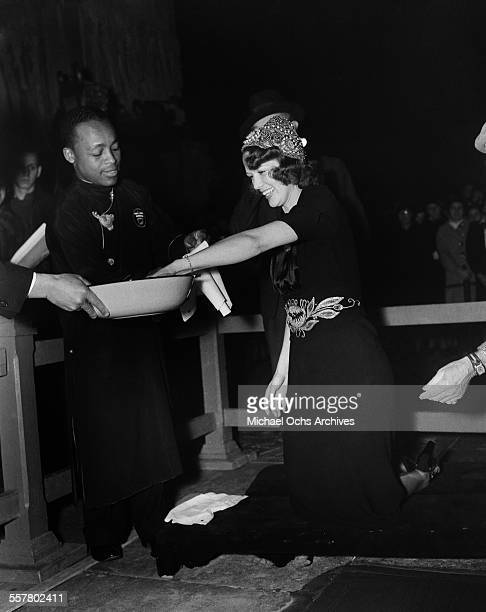 Actress Eleanor Powell cleans her hands after her hands were added to cement in front of Grauman's Chinese Theatre in Los Angeles California