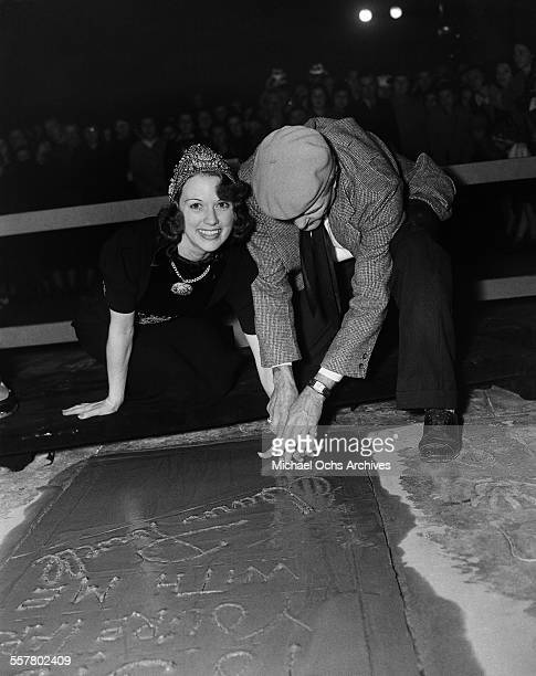 Actress Eleanor Powell has her hand print added to cement in front of Grauman's Chinese Theatre with the help of Jean W Klossner in Los Angeles...