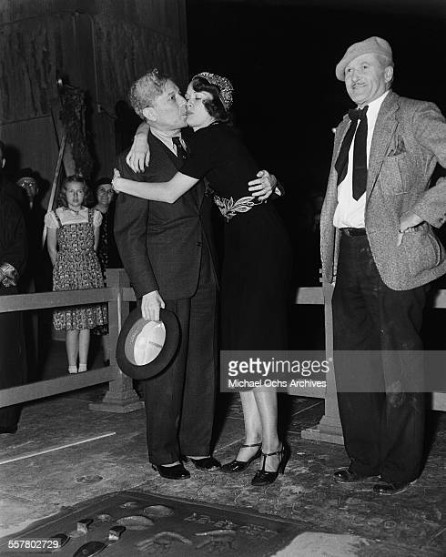 Actress Eleanor Powell hugs Sid Grauman of Grauman's Chinese Theatre after having her hand and foot print ceremony with the help of Jean W Klossner...