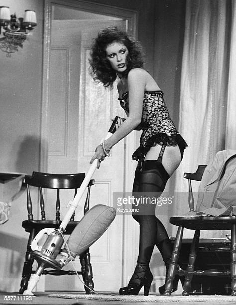 Actress Elisabeth Wiener using a vacuum cleaner while wearing suspenders and stockings in a scene from the television movie 'La p Respectueuse' 1974
