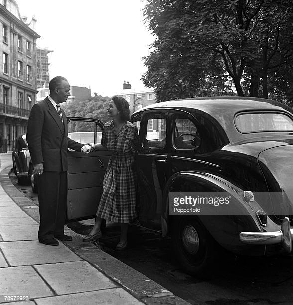 Actress Elizabeth Allan photographed with her husband by their car 1952