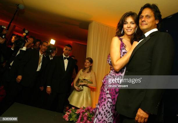 Actress Elizabeth Hurley wearing Chopard jewelry arrives with Arun Nayar at The Chopard Trophy party at Palm Beach on May 14 2004 in Cannes France...