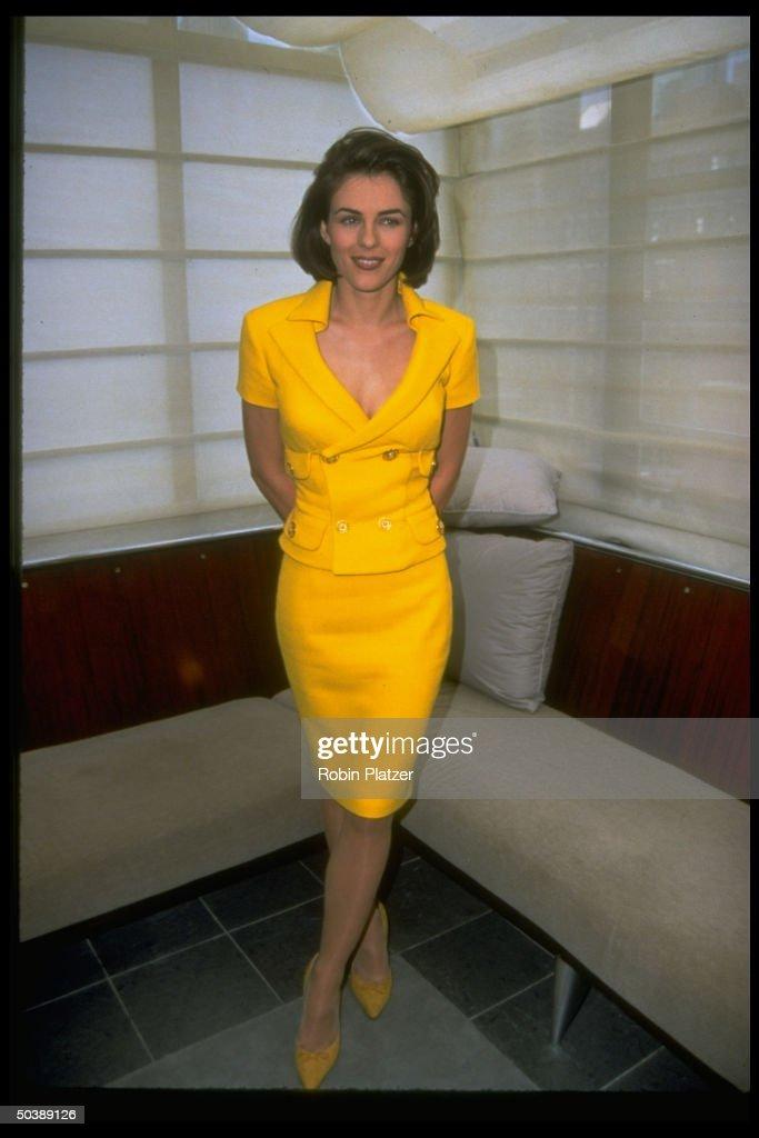 Actress Elizabeth Hurley wearing low-cut yellow suit by Versace, standing in room decorated in mimimalist-Zen style.