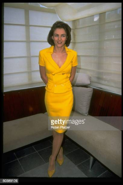 Actress Elizabeth Hurley wearing lowcut yellow suit by Versace standing in room decorated in mimimalistZen style