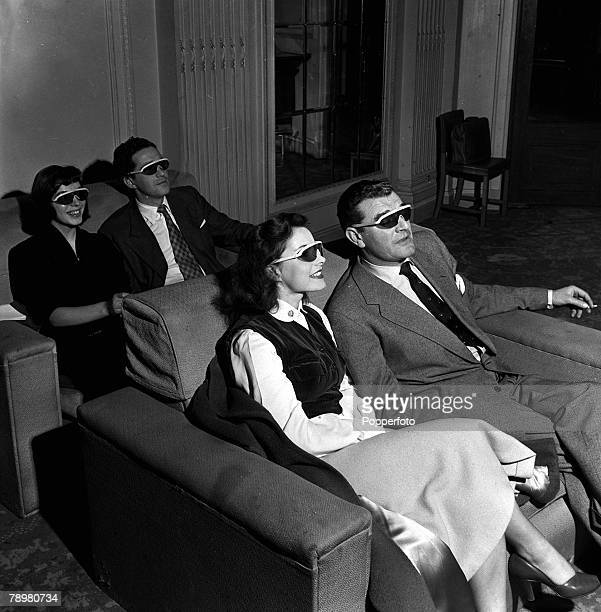 1953 Actress Elizabeth Sellars and actor Jack Hawkins with other stars watch 3D films they are wearing special polaroid spectacles