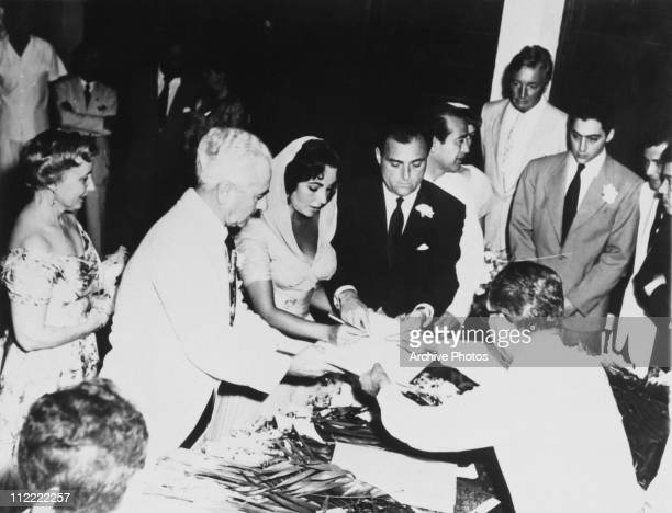 Actress Elizabeth Taylor and Mike Todd signing the register on their wedding day 2nd February 1957 Acapulco Her parents Francis and Sara are on the...