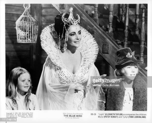 Actress Elizabeth Taylor, as Queen of Light, holding a wand between Patsy Kensit and Todd Lookinland in a scene from the film, 'The Blue Bird,' 1976.