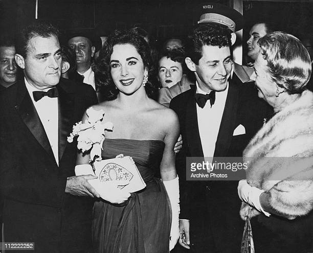 Actress Elizabeth Taylor at an event with her husband film producer Mike Todd , and singer Eddie Fisher, circa 1957.