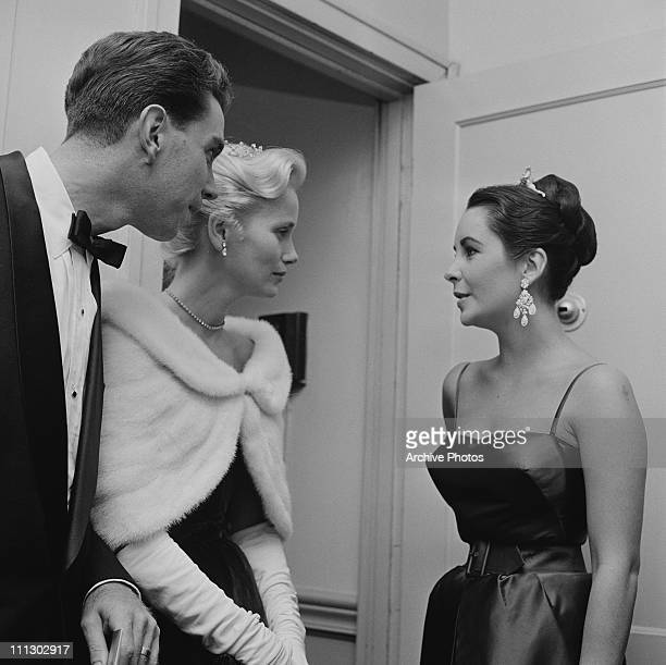 Actress Elizabeth Taylor chats with Eva Marie Saint and her husband director and producer Jeffrey Hayden at a showing of the film 'Raintree County'...