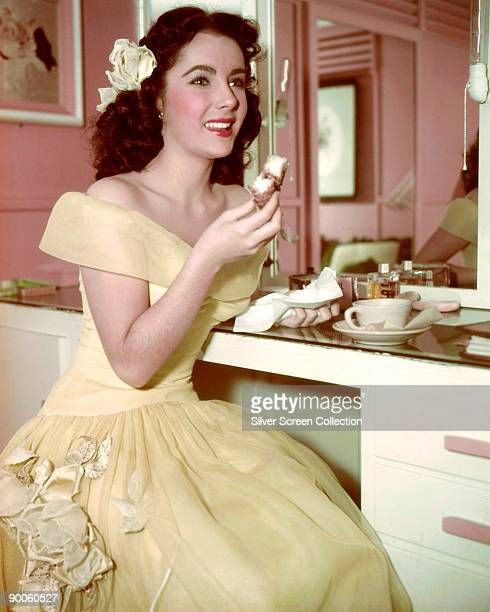 Actress Elizabeth Taylor enjoys tea and a cake in her dressing room circa 1950