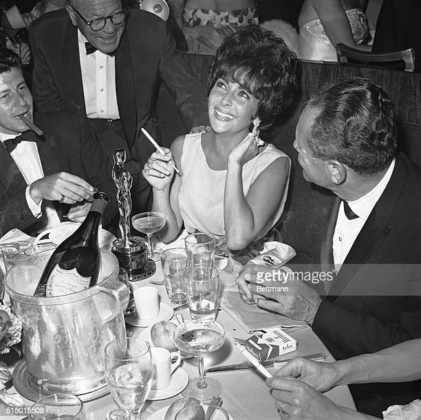 4/18/1961 Actress Elizabeth Taylor her Oscar before her demonstrates her happiness as she relaxes at a champagne party following the Oscar ceremony...