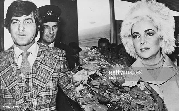 Actress Elizabeth Taylor holding a bouquet of flowers as she arrives at Amsterdam Airport with her boyfriend Henry Wynberg in the country to attend a...