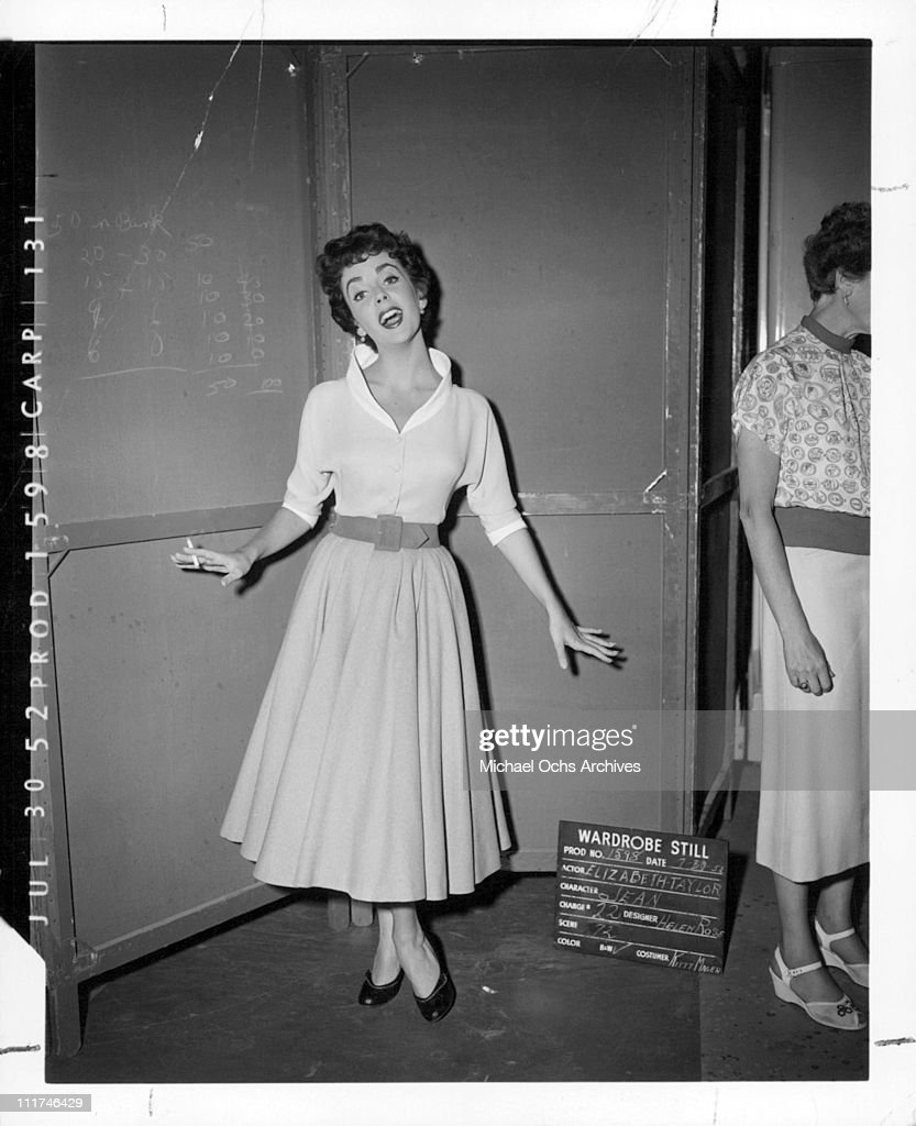 Actress Elizabeth Taylor holding a cigarette while posing in a dress designed by Helen Rose in the MGM wardrobe department during production of the film, 'The Girl Who Had Everything,' July 30, 1952.